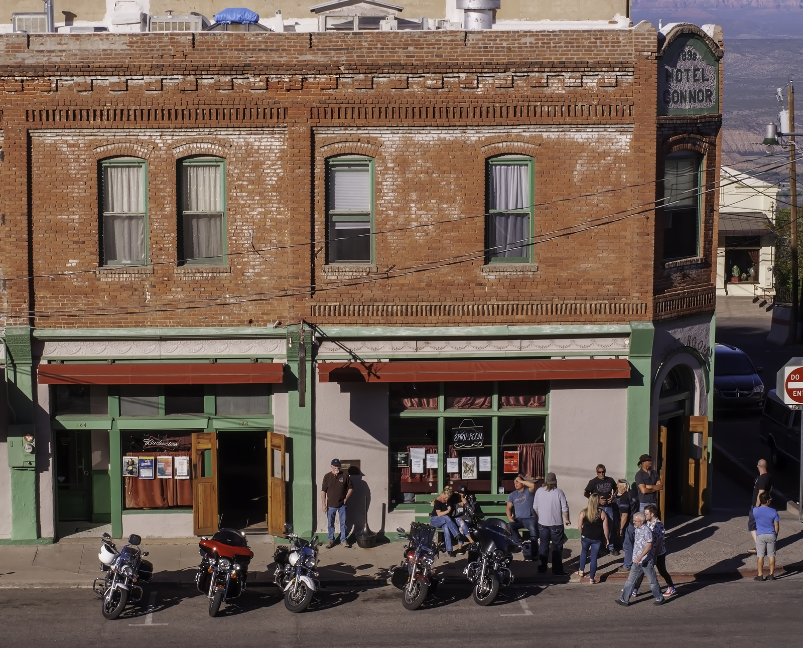 Save Download Preview Jerome, Arizona, USA 04/21/2019 People standing outside of the Conner Hotel next to parked motorcycles on the street on a sunny spring day