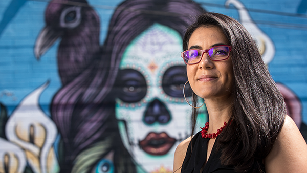 A Latina woman standing in front of a mural of a sugar skull